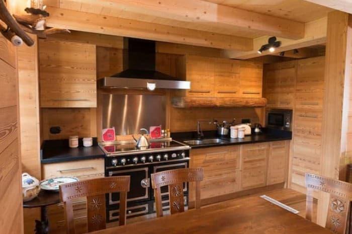 cucina-in-legno-moderna-con-ripiano-scuro-e-ampio-piano-cottura