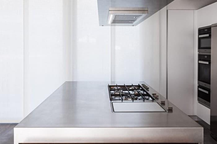 piano-cottura-di-una-cucina-moderna-con-cappa-sospesa-e-tavolo-a-scomparsa